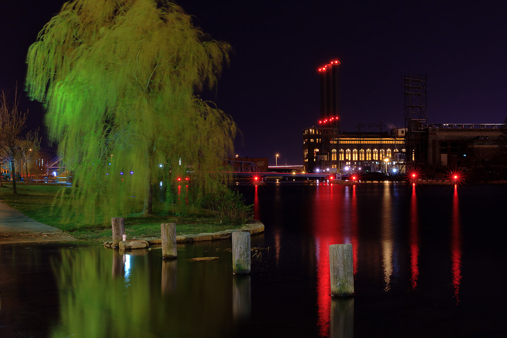 A lonely willow tree sits on the edge of the Providence River in Downtown Providence, Rhode Island. The Manchester Street Power Station in the background adds to the night landscape
