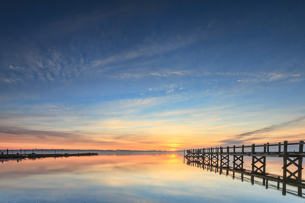 A pier stretches out into Narragansett Bay in the Edgewood section of Cranston, Rhode Island as the sun rises over the horizon